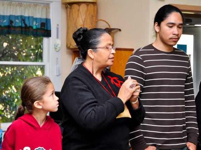 Tribal elder Dawn Dove leads the ceremony while Nkeke Harris and Christian Hopkins listen