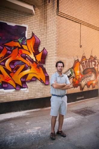 Avenue Concept founder Yarrow Thorne stands in front of a recently commissioned wall at the Roots Cafe downtown