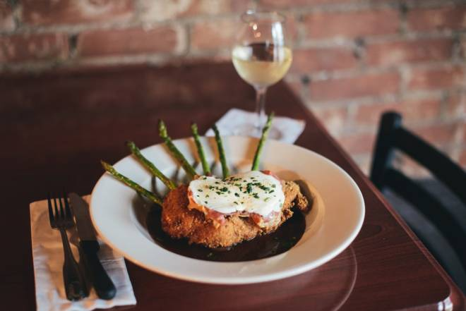 Pork Valdostana, a breaded center cut pork loin baked with prosciutto di parma, fresh mozzarella, grilled asparagus and a burgundy demi-glace