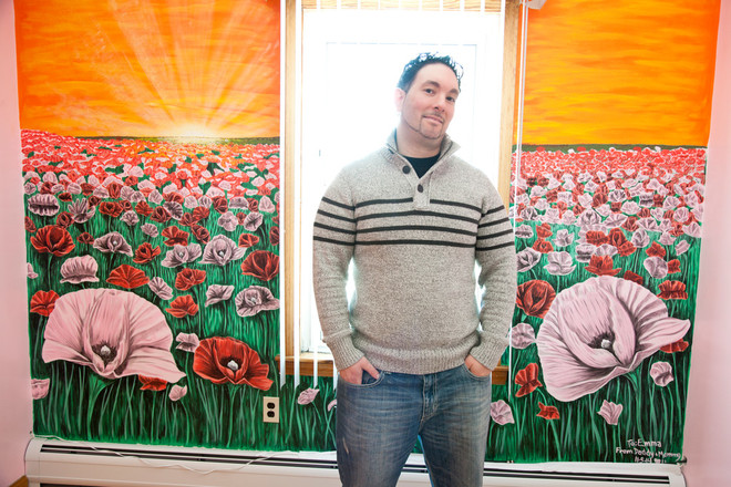 Helio Pacheco stands in front of one of his murals