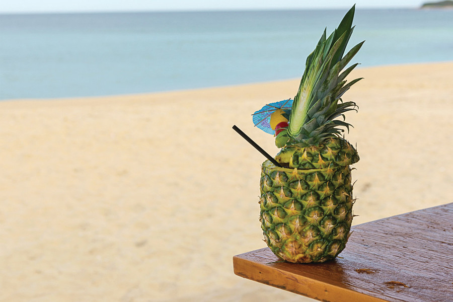 Summer perfection is a cocktail in a pineapple at Ballard's Beach