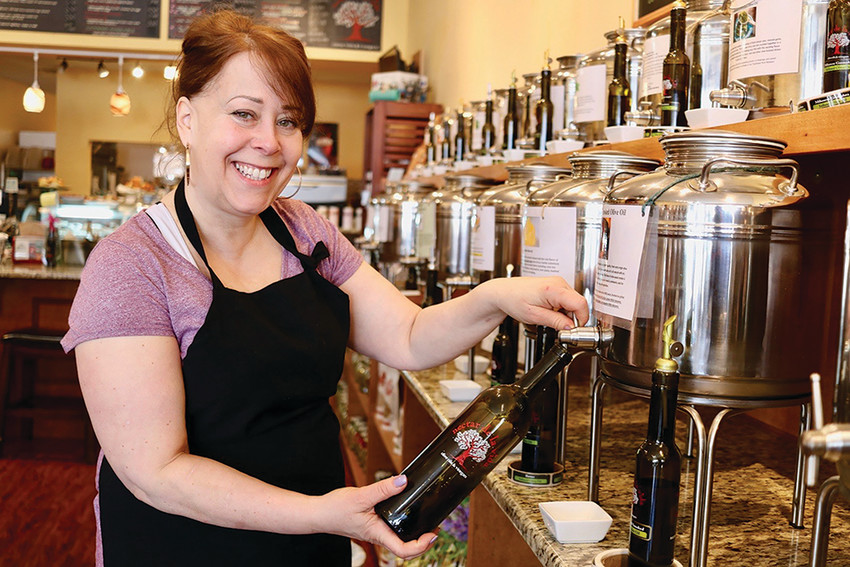 Maureen Botelho pours her own brand of olive oil at Nectar de la Vida in Warren