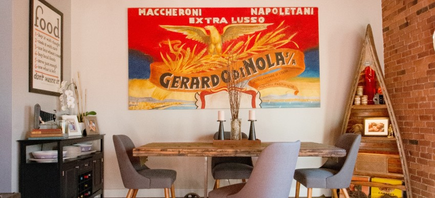 The Italian pasta company painting over the table and chairs, along with an area rug below, work together to create a dining area in the open space