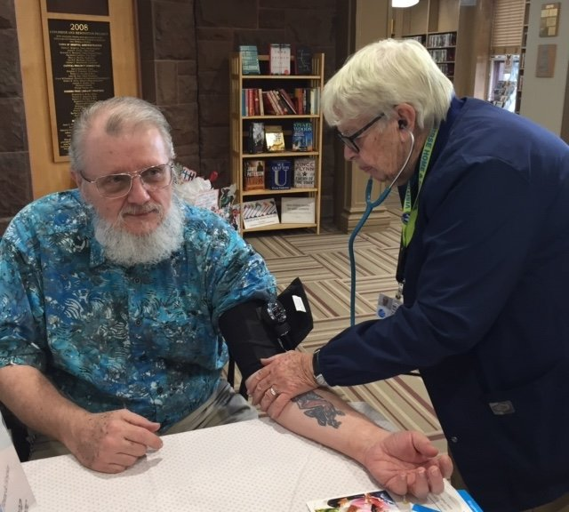 Sister Ellen Martin checks Rei Battcher's blood pressure at one of the library's free screenings