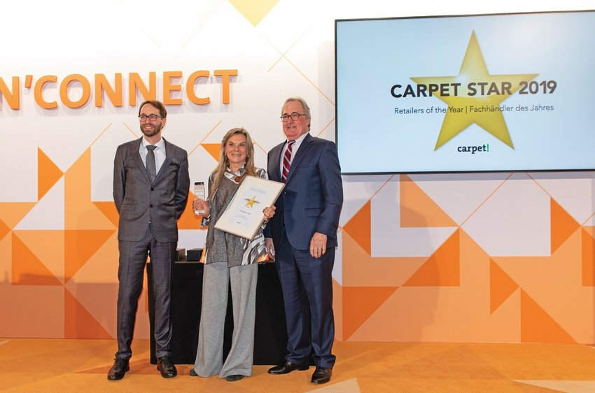 Roz Rustigian accepting the Carpet Star 2019 award: with Tim Steinert of Carpet! magazine and presenter Rob Leahy, owner of Fine Rugs of Charleston
