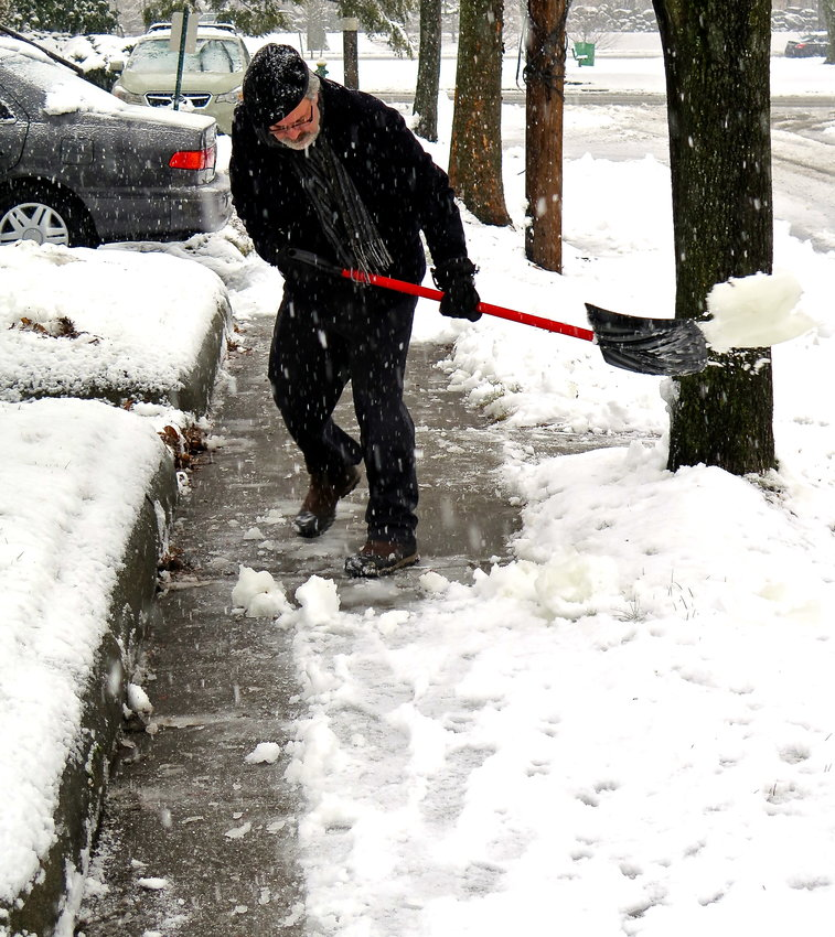 Tom Schmeling clears the walk of someone who couldn't after a big snow storm