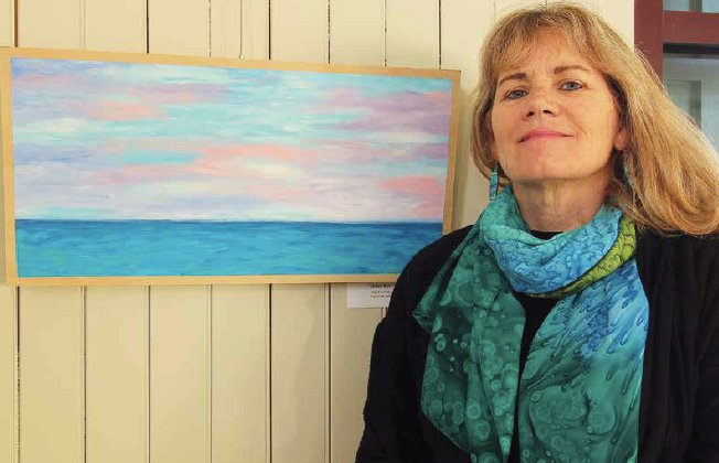 Artist Helen Roy with her acrylic on wood piece, Watch Hill Sky, on display at the newly repurposed Westerly Train Station