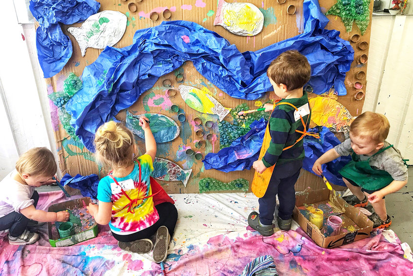 Little artists collaborate on projects like this cardboard wall, covered in everything from tinfoil fish to crumpled paper waves