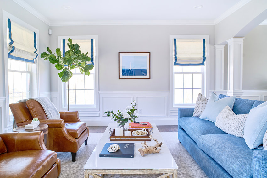 Linen shades with blue trim infuse the bright space with seaside   appeal while connecting with other like-colored elements from furniture to textiles to artwork