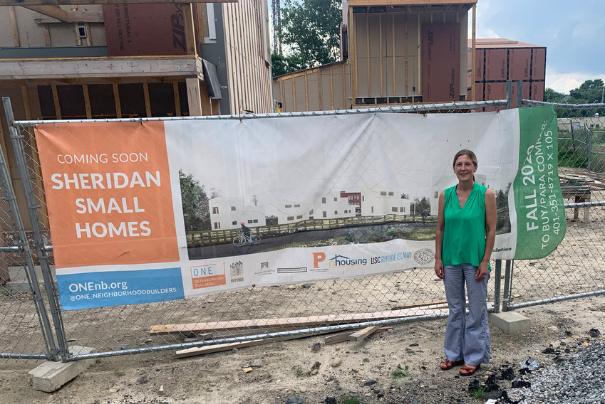 Executive Director Jennifer Hawkins stands in front of the latest development by ONE Neighborhood Builders