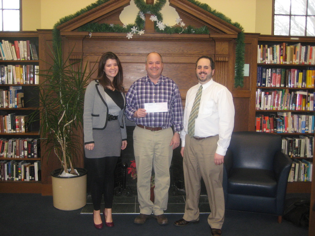 Providence Community Library Development Director Steve Kumins (center) accepts the money raised at Providence Monthly's 10 to Watch Party from PM staffers Samantha Gaus and John Taraborelli