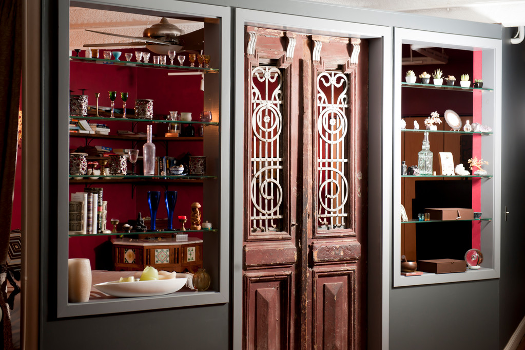 """Those are antique Egyptian doors I bought at Kyureo here in Providence. I had the wall built around the doors. The objects on the glass shelves are mostly glass and statues I have collected in markets I visit when I travel."""