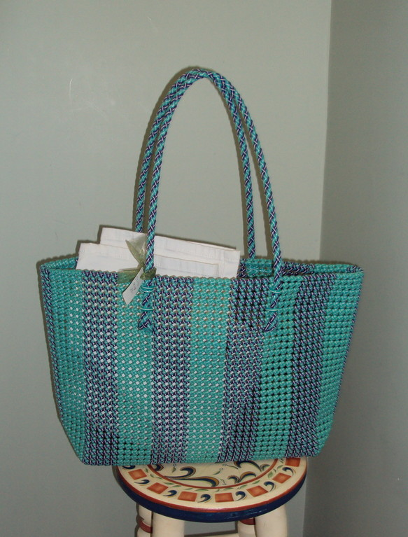 This blue beach tote is made of recycled plastic. These bags from the Sevya company are handmade by Indian women, and the profits are used for development programs throughout India. This one is great for trips to the beach because it's large enough to carry your towels, sun block, and whatever else you need to enjoy a sunny day by the water. The bright colors are perfect for summer, making it an ideal beach-day accessory. 