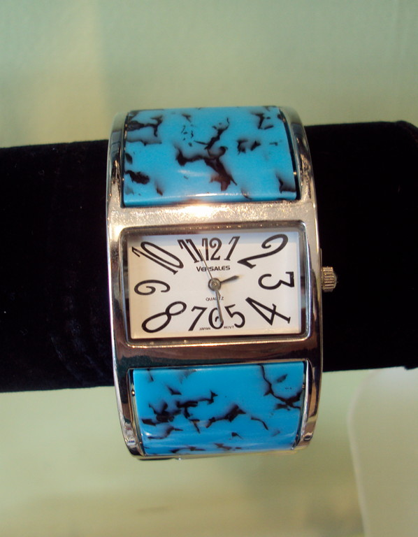 A cool and useful accessory adds a funky color accent to your outfit. This watch is ideal for the individual that doesn't want the same boring band you see on every other wrist. The face is square, and the faux turquoise stones don't completely wrap around. This feature, plus its slim design, gives the unique illusion of a bracelet instead of bulky wristwatch. 