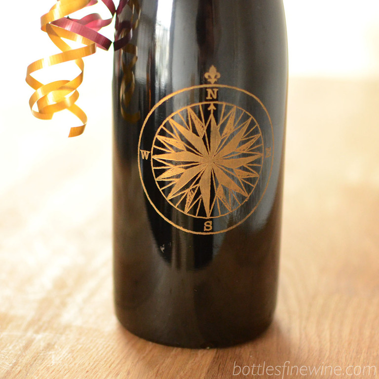 A detailed compass design engraved on a red wine bottle. Add a personalized message underneath for just $15. Order now!