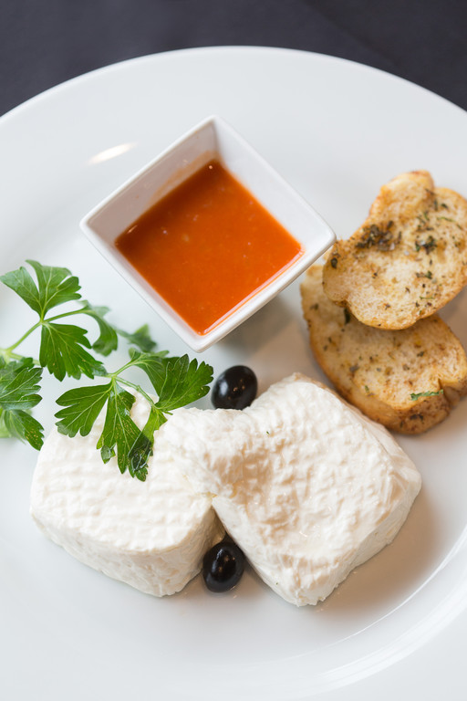 Fresh goat cheese with a freshly ground red pepper sauce and garlic toast at Caldeiras