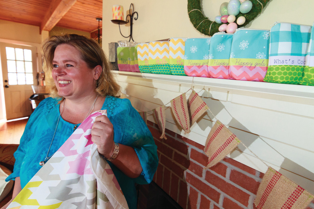 Lori Craffey shows a fabric which will be used to make the bags on the mantle behind her.
