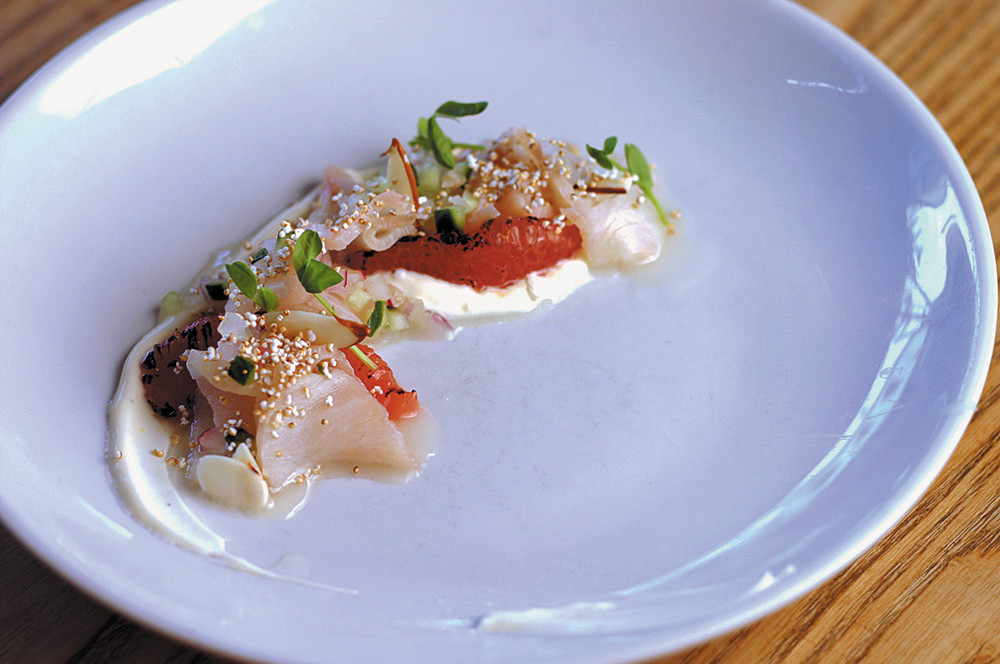 Hamachi sashimi with burnt grapefruit, passionfruit crème and uzu cured almonds