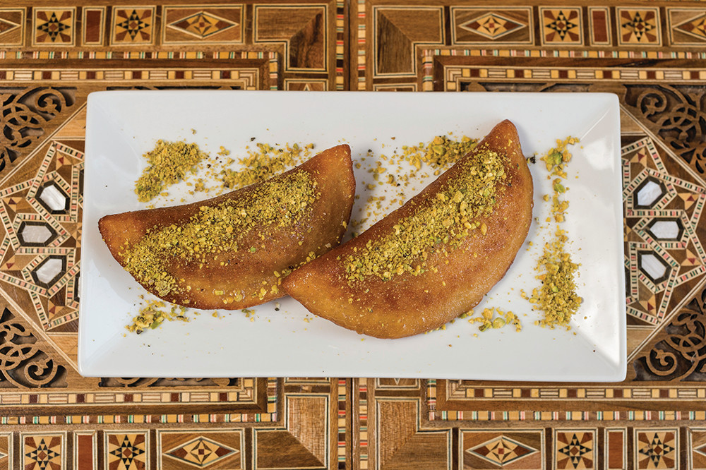 Qatayef topped with pistachio and glazed with honey