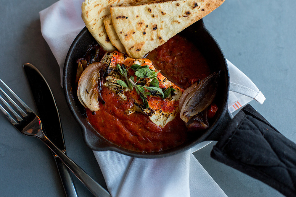 Baked feta cheese with roasted tomatoes, served with grilled pita bread