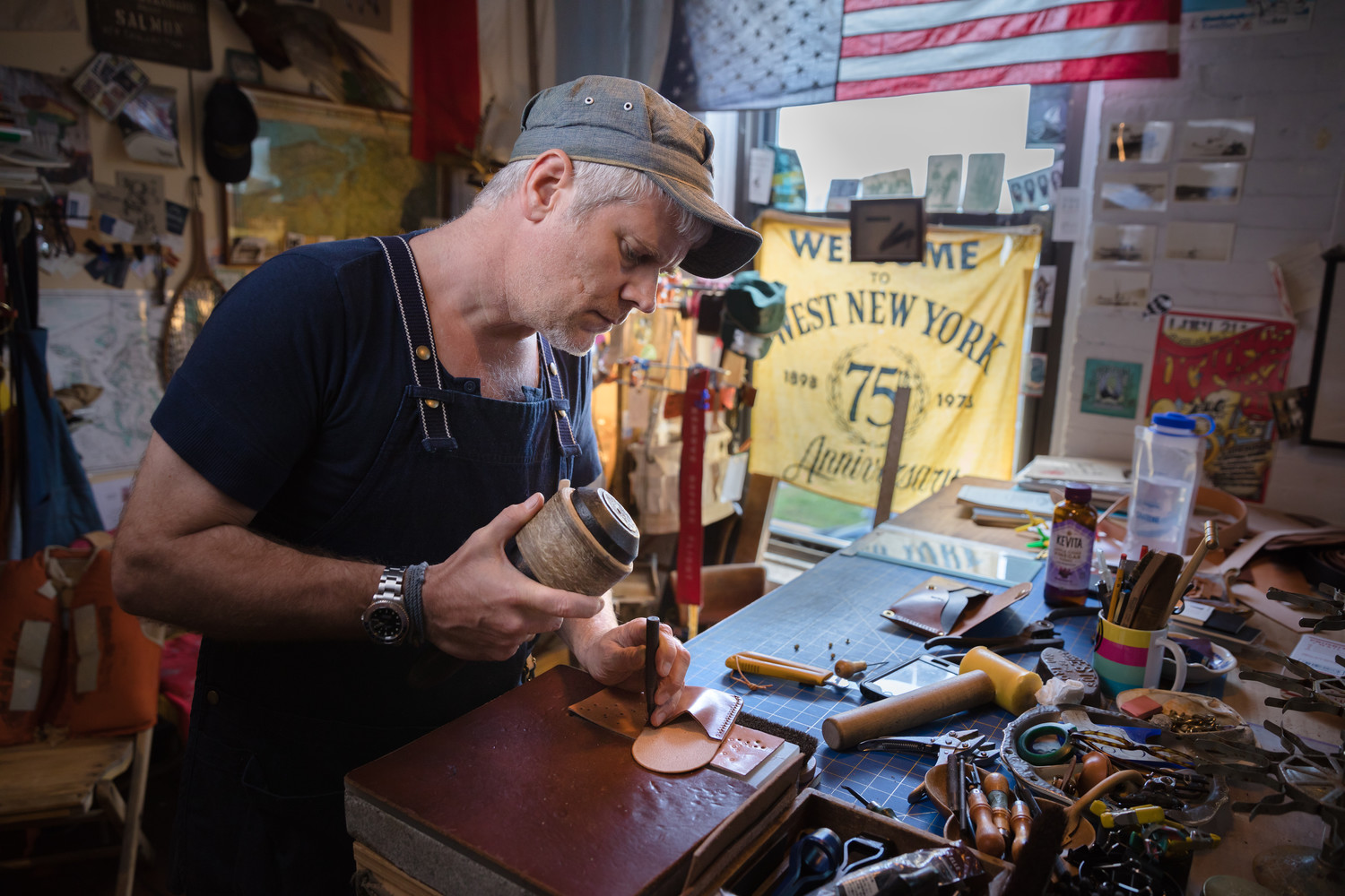 Leather artist Michael Todd Moen of Sweettrade crafting leatherwork for his online store-front in his Warren-based studio.