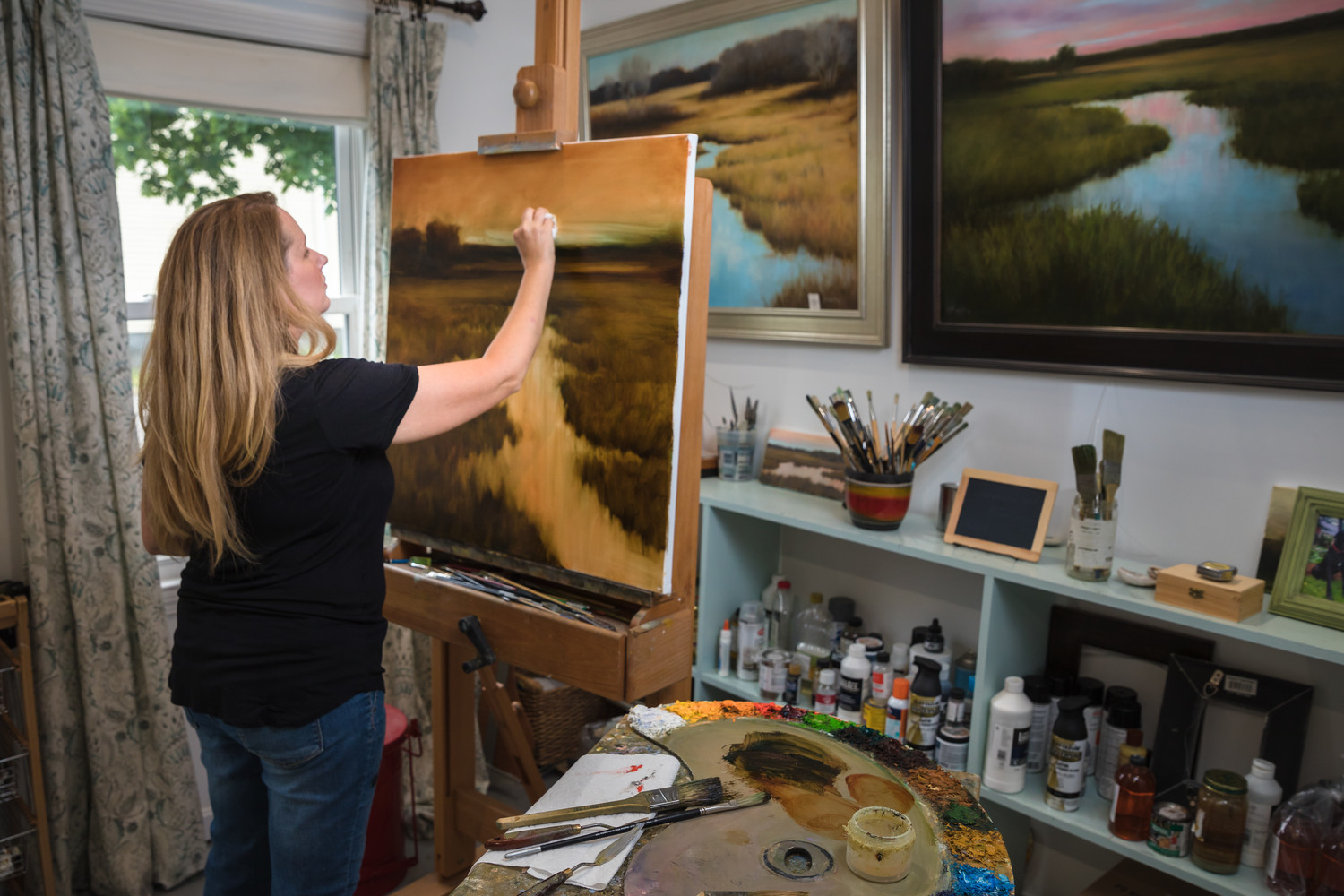 Artist Karen Murphy painting an East Bay inspired landscape to add to her collection in her East Providence studio.
