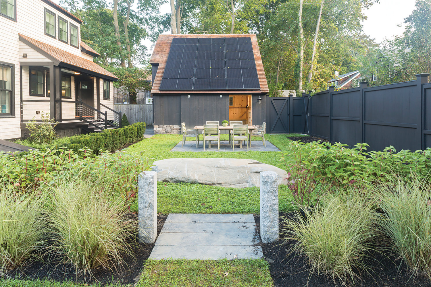 The Jamestown Net-Zero Home features a 5.5 kilowatt solar panel system from Vivint Solar to offset the energy use. A dark, earth tone shingle complements the black panels and keeps them from upstaging the well manicured backyard oasis