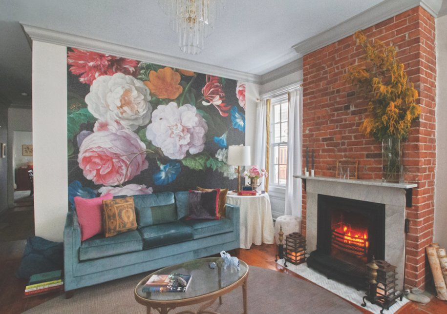 An expansive wallpaper mural based on Dutch Masters artwork creates a stunning backdrop in the living room
