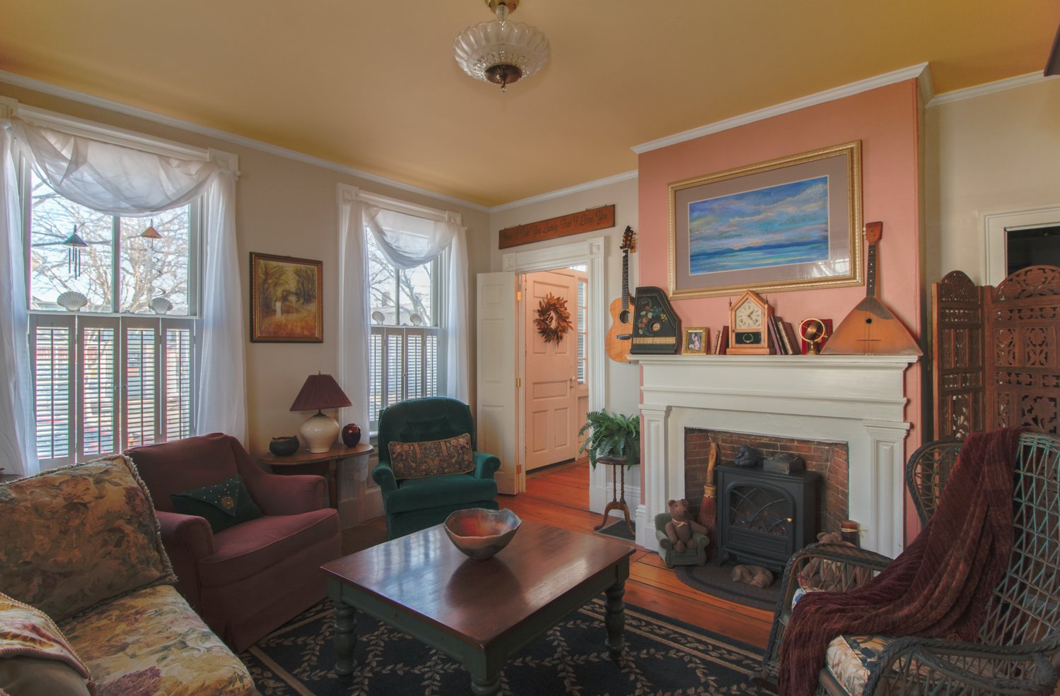 The narrow wall above the fireplace, painted a muted salmon, provides a striking backdrop for the seascape painting while connecting with the floors below