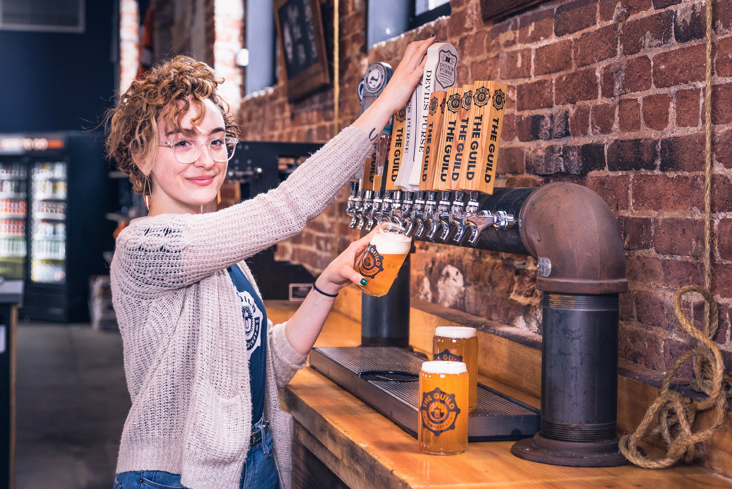Bartender Gabrielle McCauley pours a pint of one of The Guild's eight craft beers brewed onsite in Pawtucket