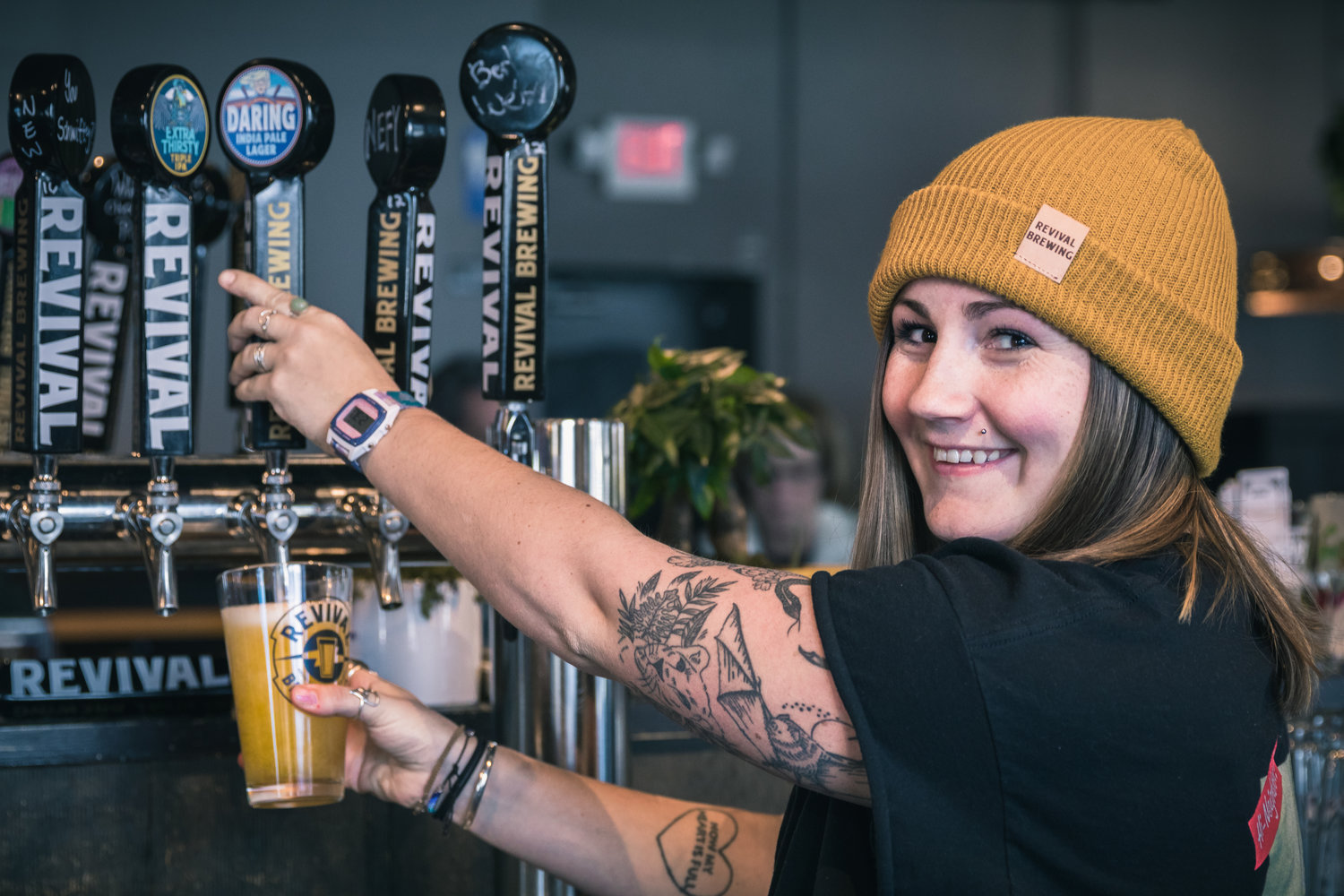 Bartender Lily Coughlin serving up cold pints in the Tap Room at Revival Brewery