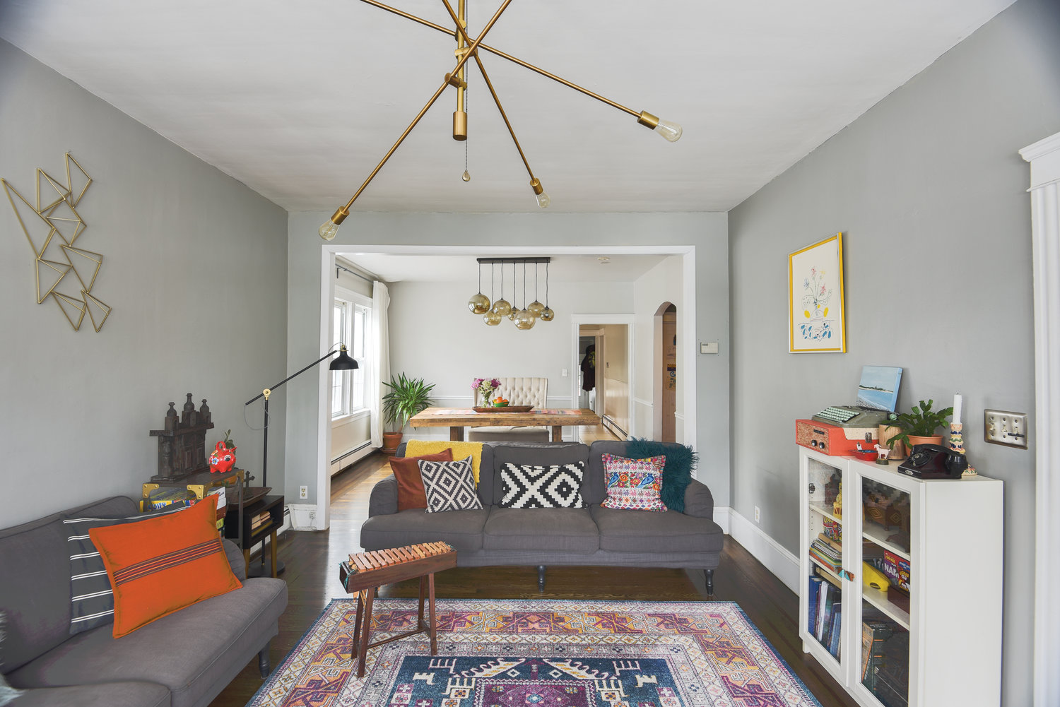 Soft gray walls and simple furnishings provide a neutral backdrop for a mix of colorful patterned textiles