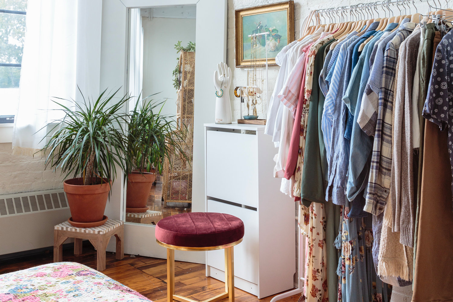 A garment rack stands in for closet space.