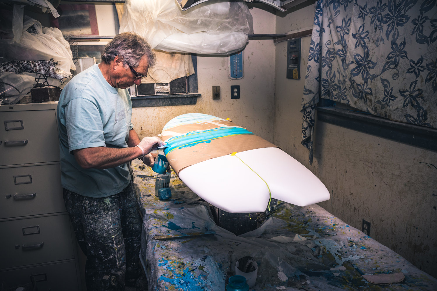 Dave Levy, of Levy Surf Designs applying paint to a board.