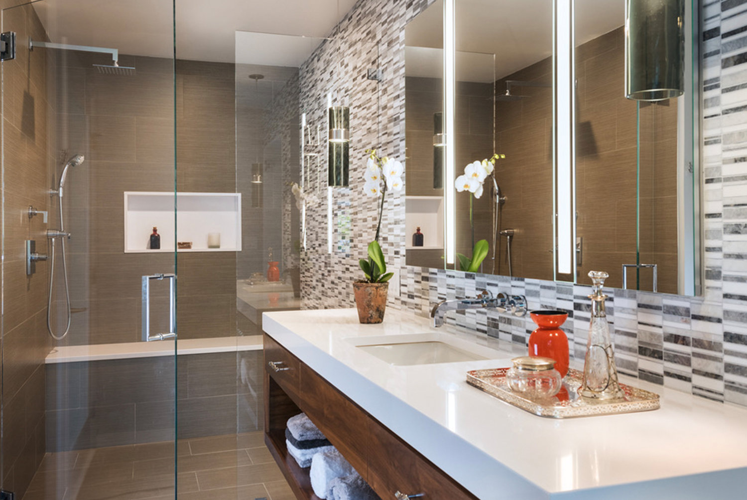 A calming palette of white counter tops, gray and white mosaic stone and glass, and mocha porcelain floors, keeps the single-windowed bathroom light and bright.