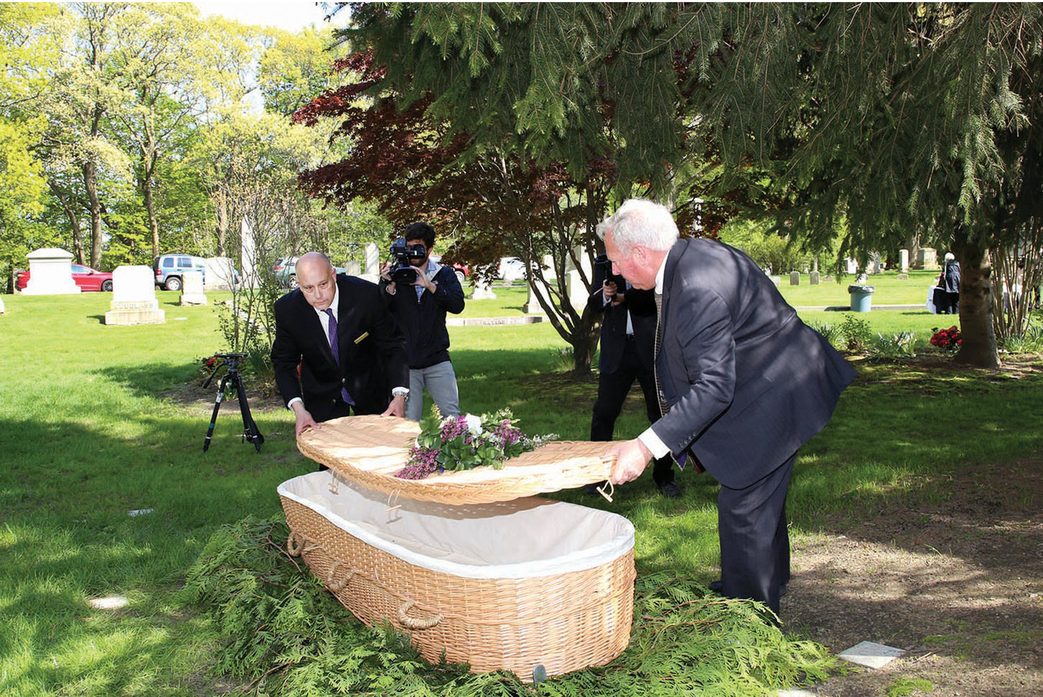 Swan Point staff demonstrates the closing of a wicker casket, which is made of wholly biodegradable materials