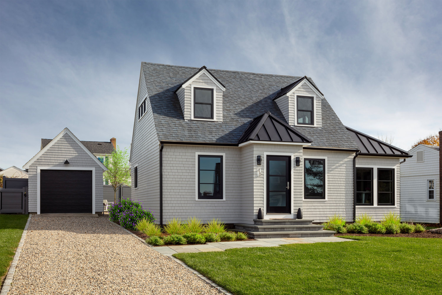 Both inside and out, a prescribed use of black elements frame neutral colors adding interest and sophistication to the humble  Cape Cod style home.
