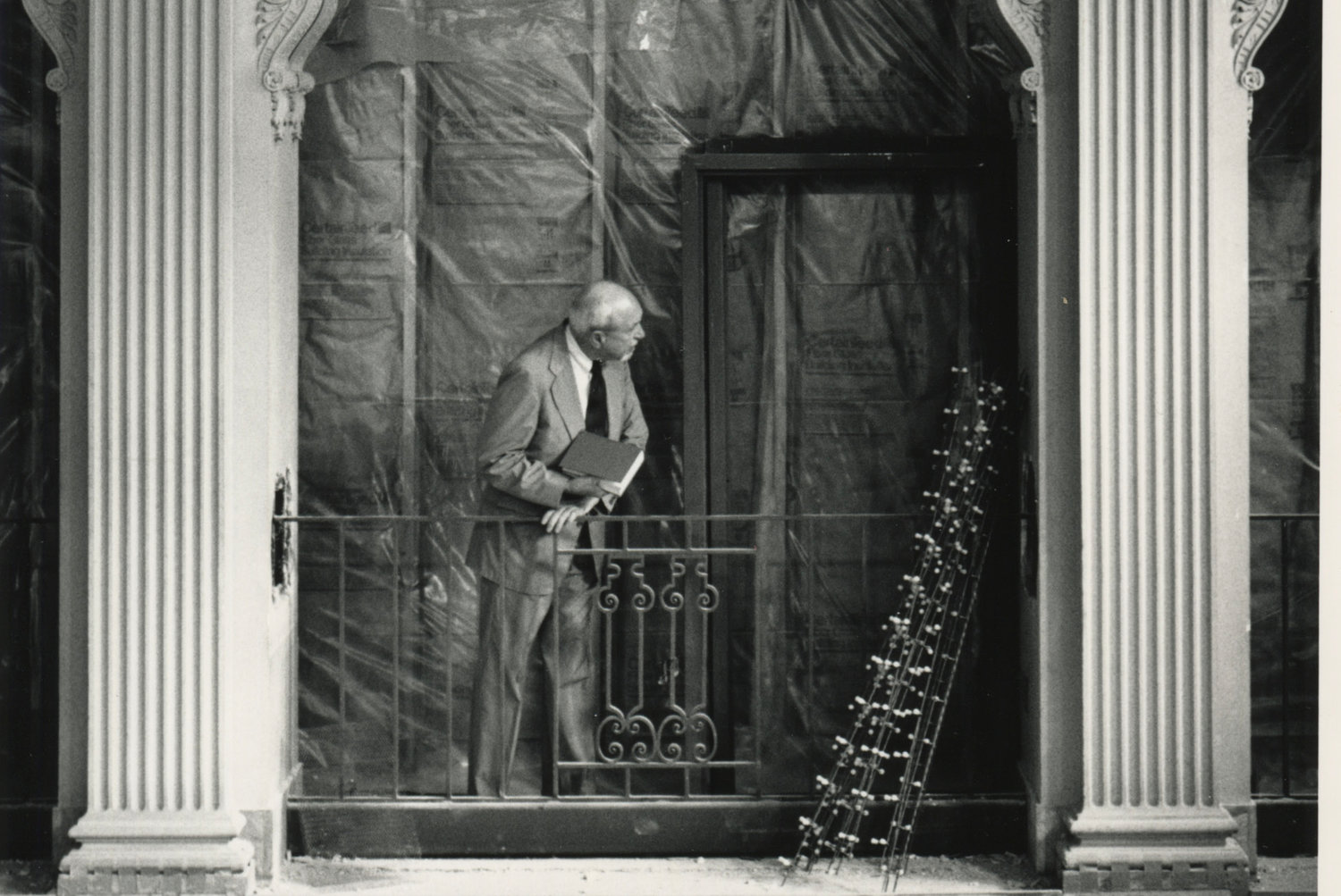 A man looking over the renovations of the Grand Hall of the Providence Public Library. He stands between the railing of the balcony of the Grand Hall and a wall of fiberglass that is enclosed in plastic.