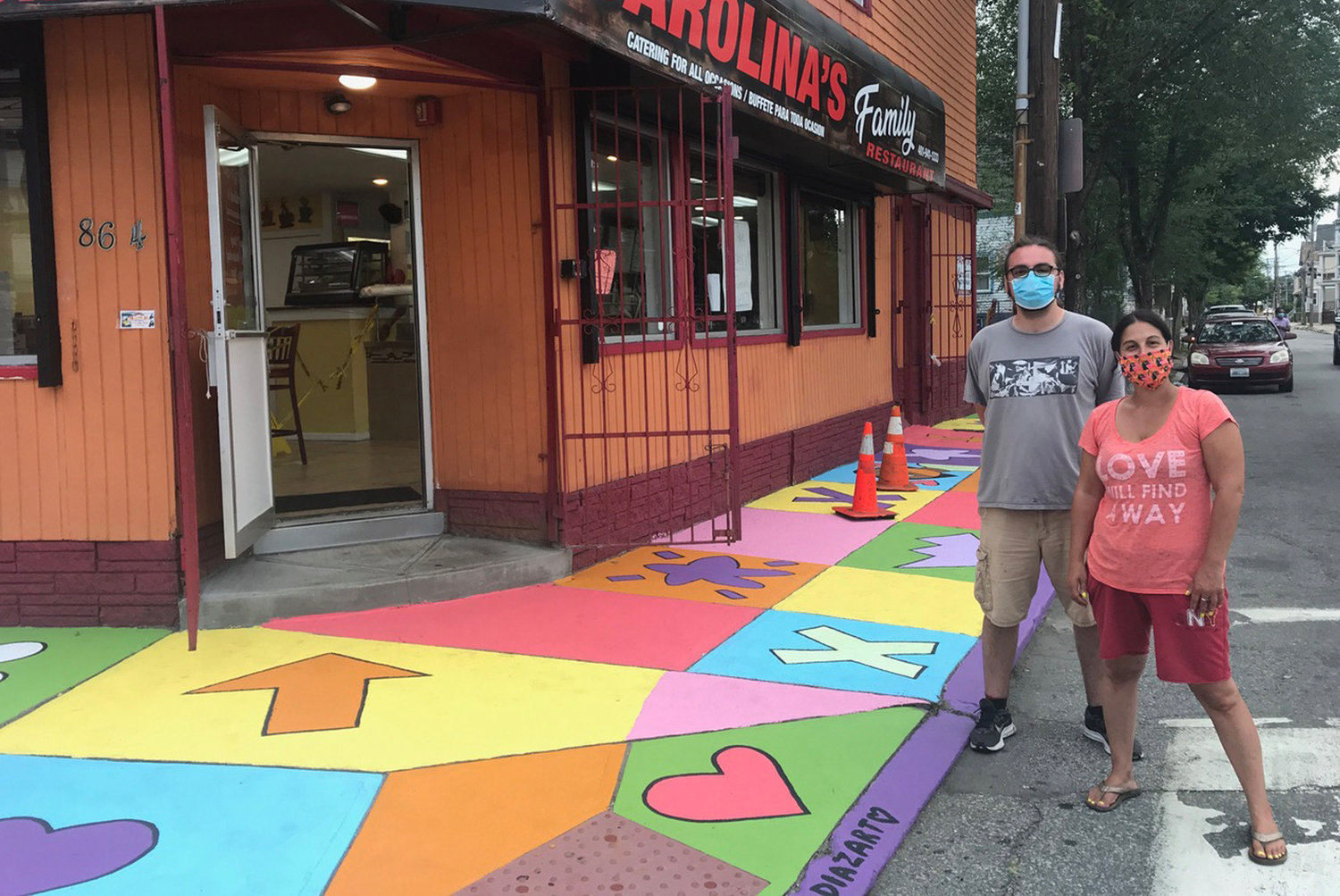 Artists Pablo Youngs & Tamara Díaz stand before finished sidewalk art, corner of Oxford and Broad Streets