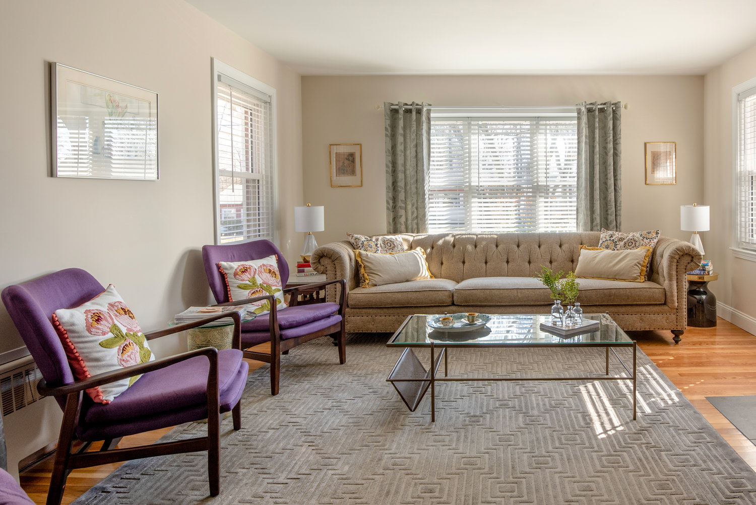 A pair of violet chairs infuses rich color into the neutral palette