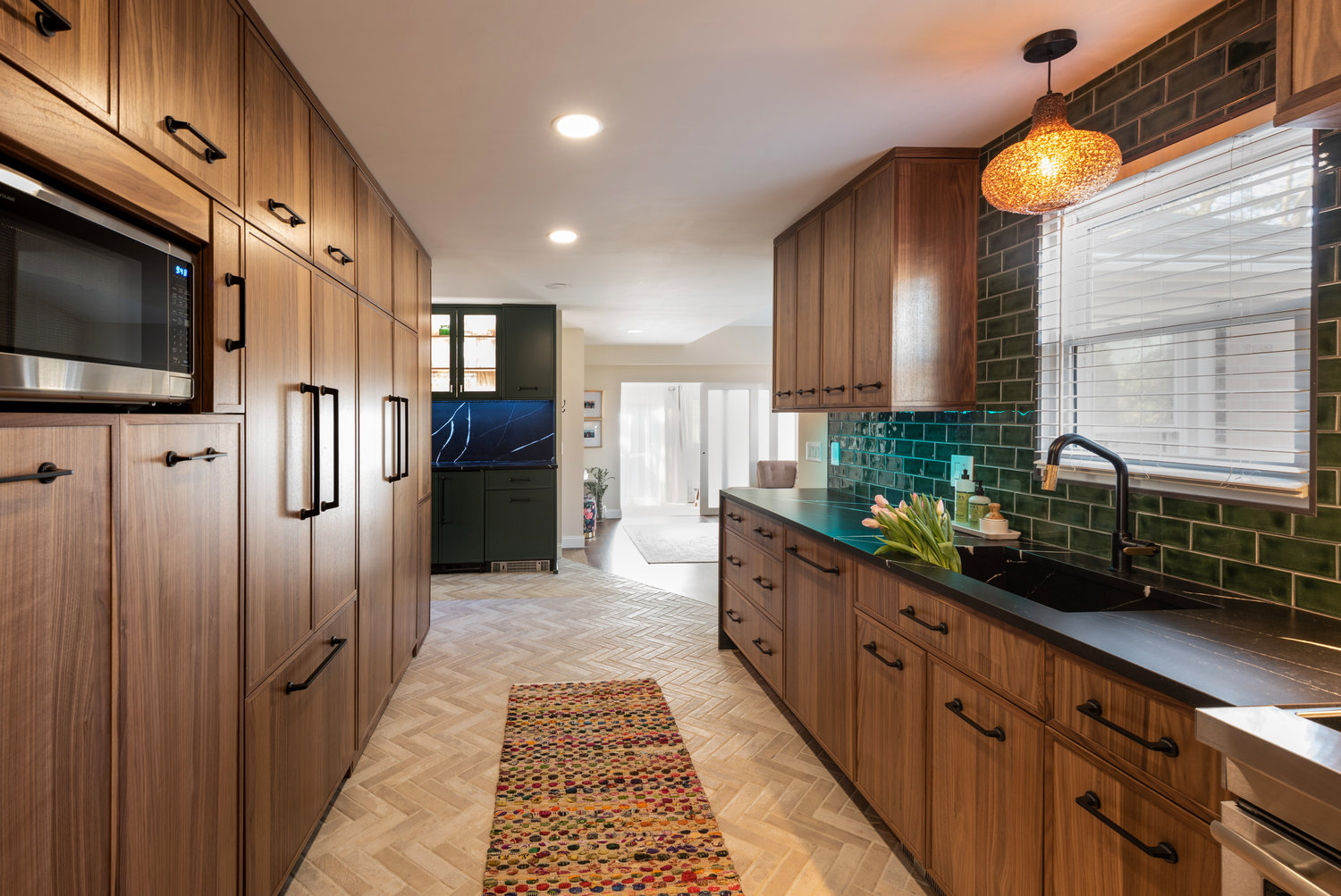 The emerald green ceramic tile backsplash is stunning against wood features