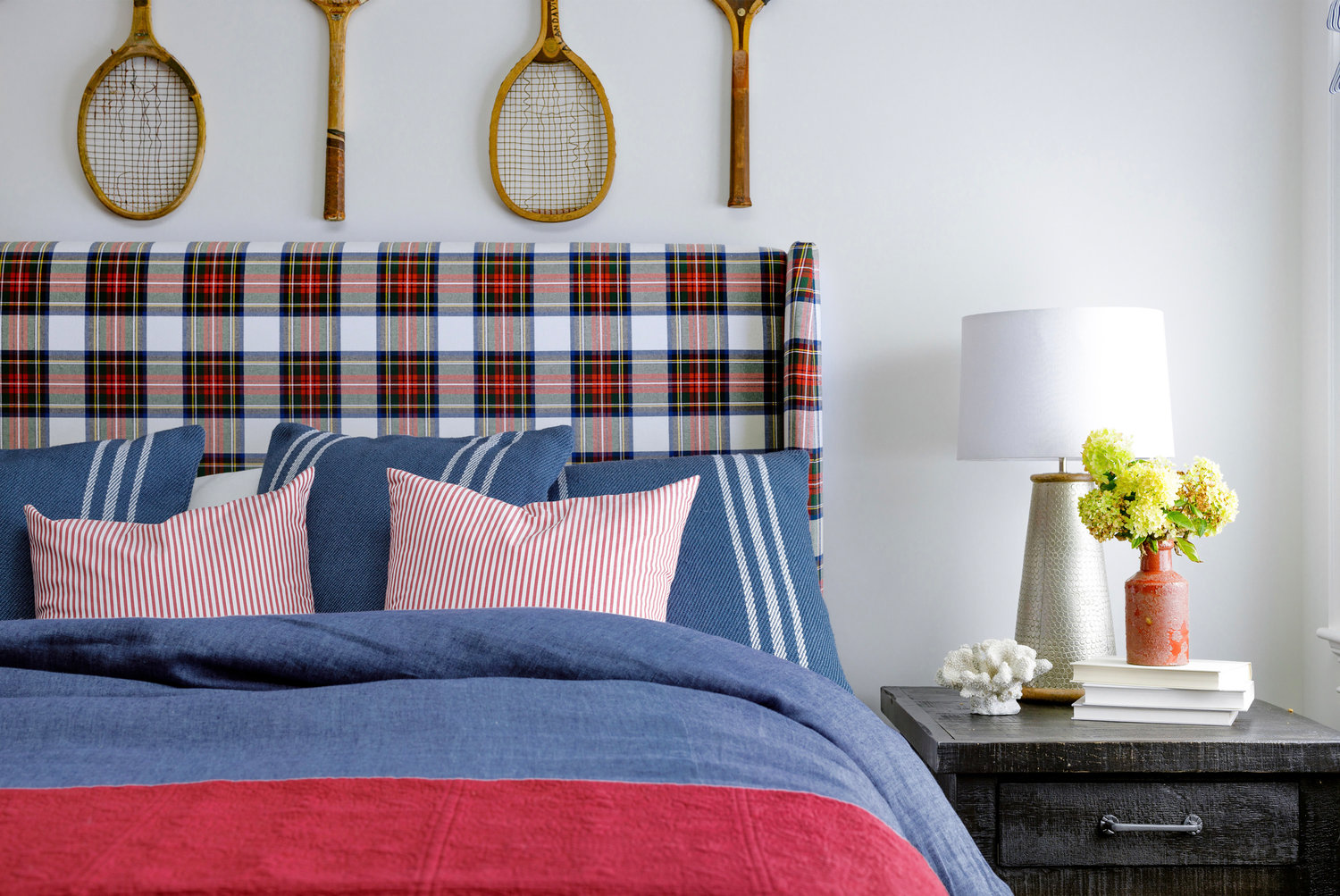 The tartan headboard and base lend instant collegiate spirit to this bedroom; a foursome of vintage tennis rackets make for inspired wall art with NPT ties