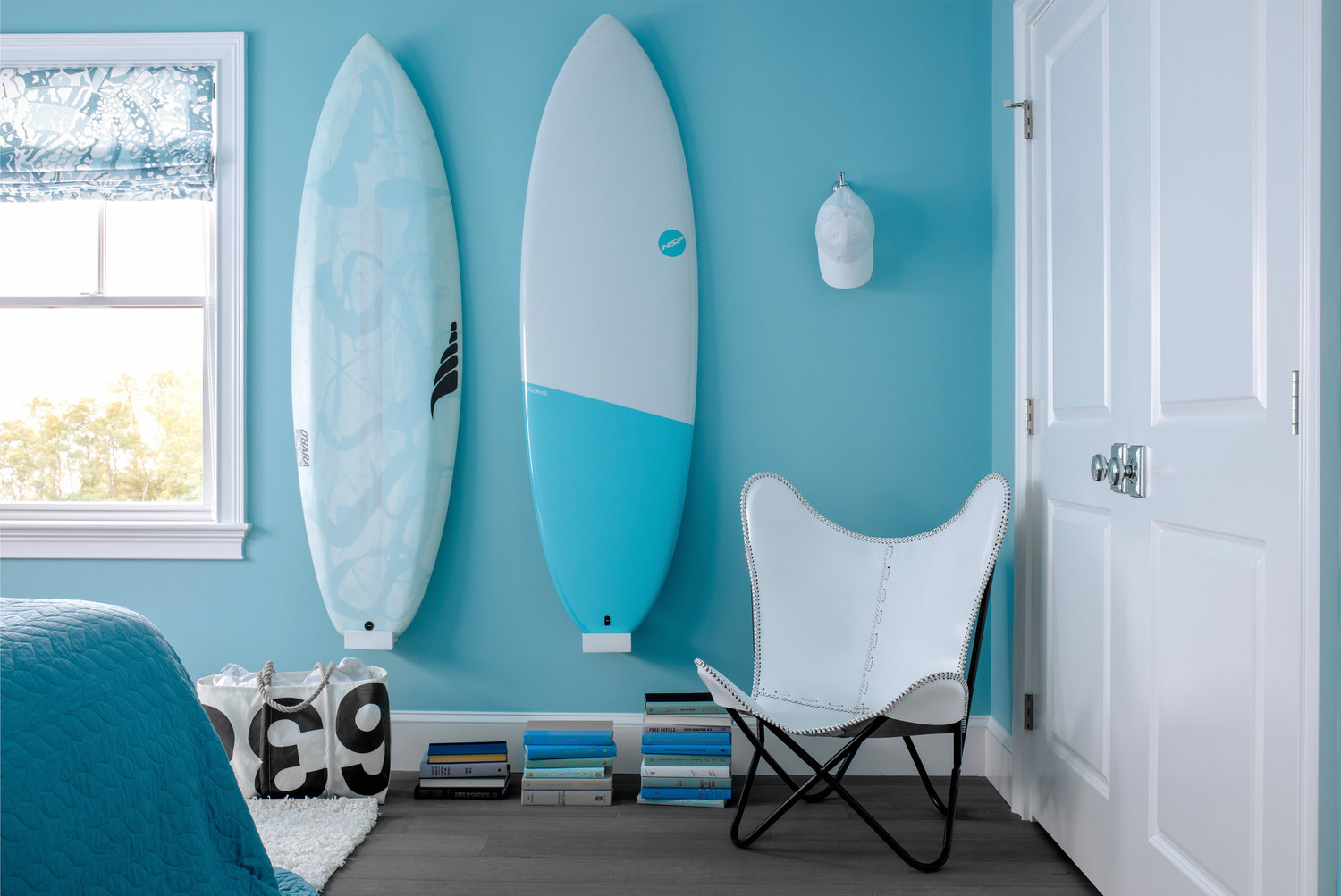 Ocean State surf culture was the inspo for the aqua guest bedroom, while accents in black and white keep the look grounded