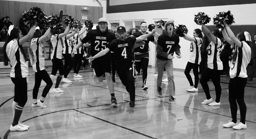 The Quilcene Rangers football team charges into the gymnasium, flanked by the school's cheerleaders, during Friday's homecoming assembly, capping off their Spirit Week.