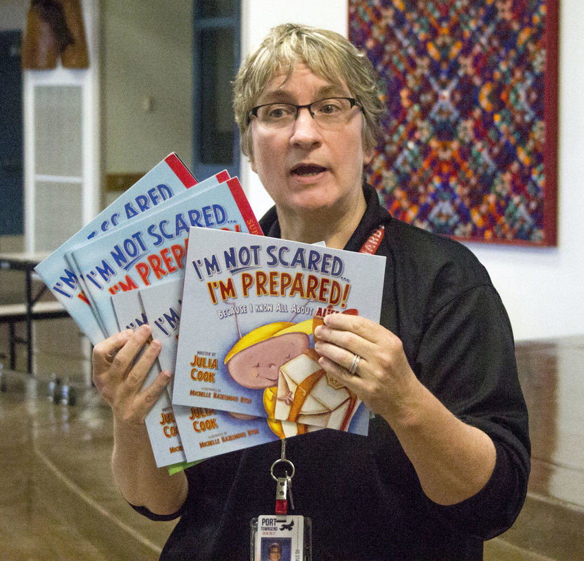 PTHS Principal Carrie Ehrhardt shows off emergency preparedness books for K-2 students. Leader photos by Kirk Boxleitner