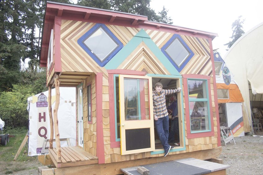 """Community Boat Project student Xander Reeves shows off the paint job he applied to the CBP's second annual """"Tiny House"""" project. Leader photo by Kirk Boxleitner"""
