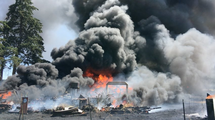 Firefighters arrive to find a structure in flames and approximately 1.1 acres surrounding it burned in the 100 block of Center Road in Chimacum at 2:06 p.m. July 26. Photo courtesy of Bill Beezley