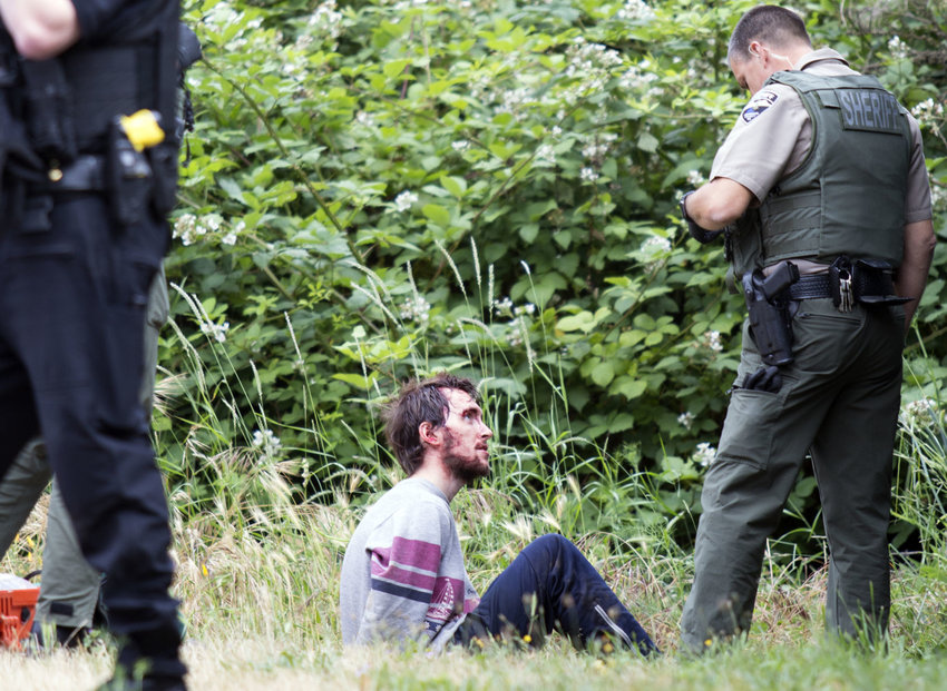 Wrists cuffed behind his back, face covered in blood, stabbing suspect Matthew Malone, 22, talks with a Jefferson County Sheriff Deputy at about 9:30 a.m. the morning of July 1. Malone was taken to Jefferson Healthcare after the incident for evaluation. The victim, a 57-year-old male, was flown to Harborview Medical Center in Seattle.