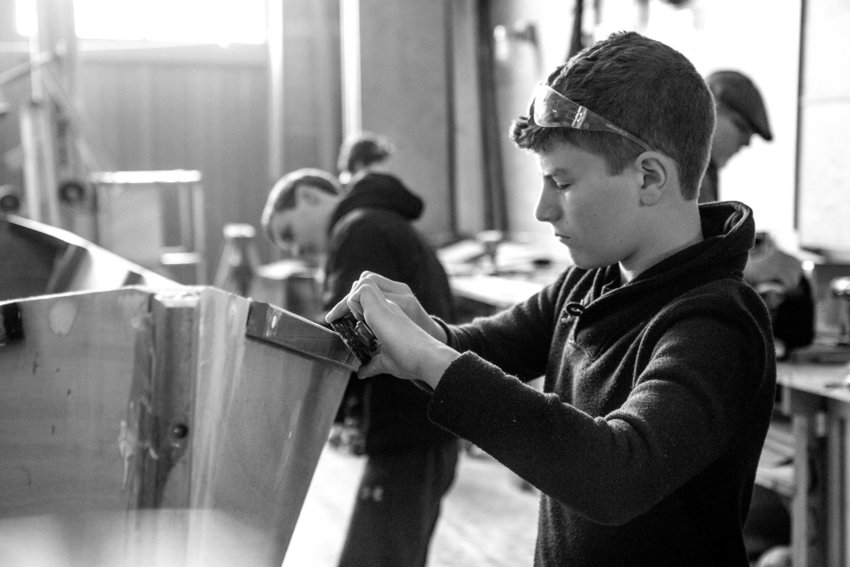 Samuel Holmes works on sanding a boat he and his fellow classmates built and launched June 1.