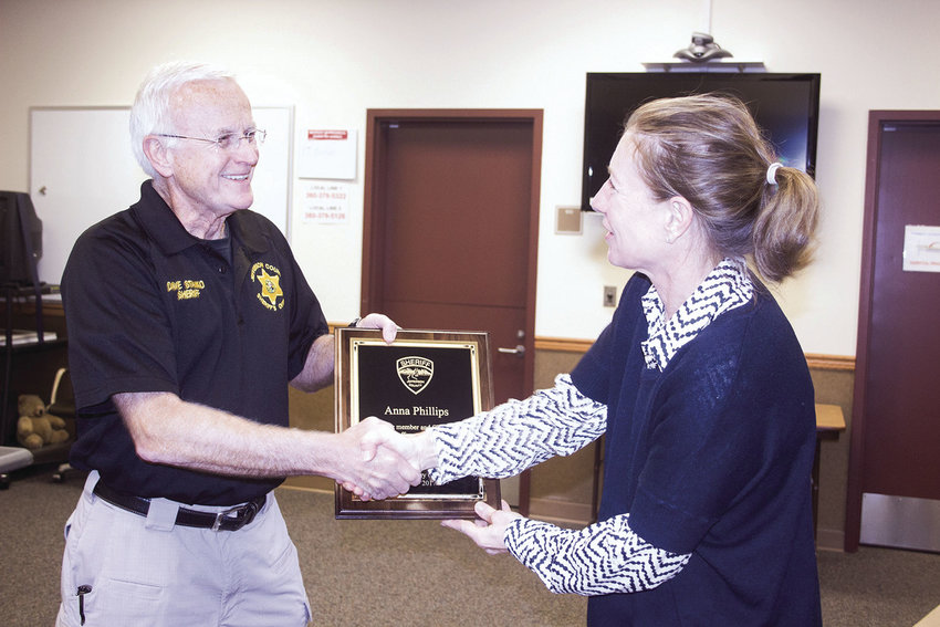 Jefferson County Sheriff Dave Stanko presents a plaque to Anna Phillips, outgoing chair of the Sheriff's Citizens Advisory Committee, before a new chair is elected by the committee Nov. 2. Photo by Kirk Boxleitner